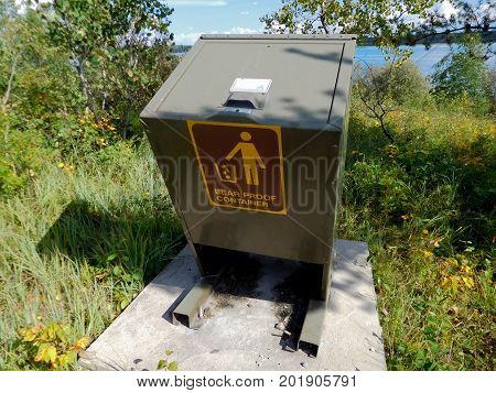 A bear proof garbage container by a lake.