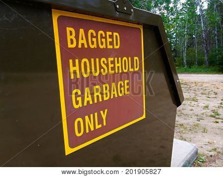A Household Garbage Only Sign on Dumpster.