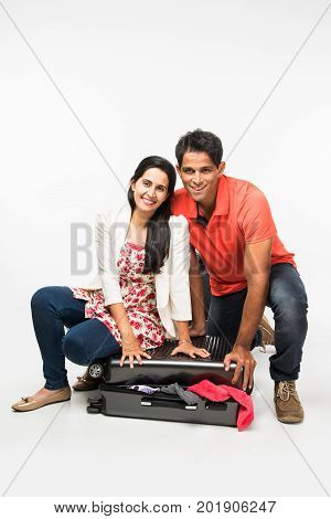 stock photo of indian young Couple packing for holiday, trying to close suitcase full with clothes, sitting isolated over white background