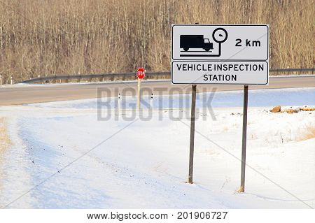Vehicle Inspection Ahead Sign With Highway In The Background