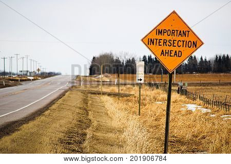 An important intersection ahead warning sign along a highway