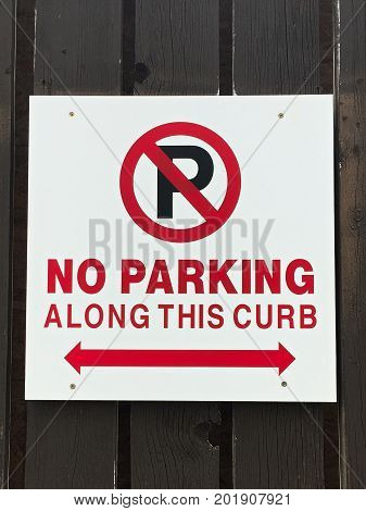 A no parking along this curb sign on a wooden fence