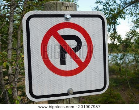 No Parking Sign Against a Forest Background.