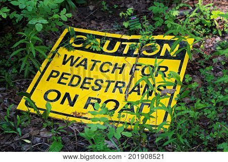 A Caution Watch For Pedestrians On The Road Sign Laying On The Ground