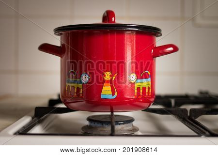 Red saucepan on the gas stove. Kitchen pot on the gas stove.