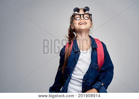 little girl smiling with a backpack on a gray background.