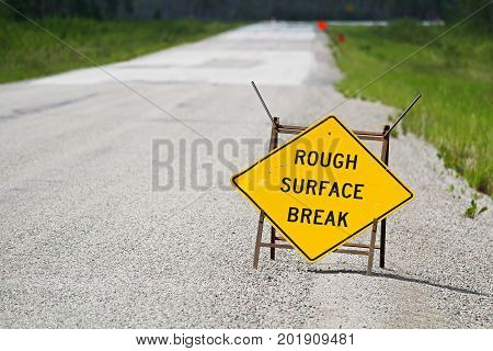 A Yellow Rough Surface Break Sign With A Road Blurring Into The Background