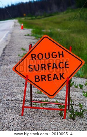 An Orange Rough Surface Break Sign With Construction Pylons Behind It