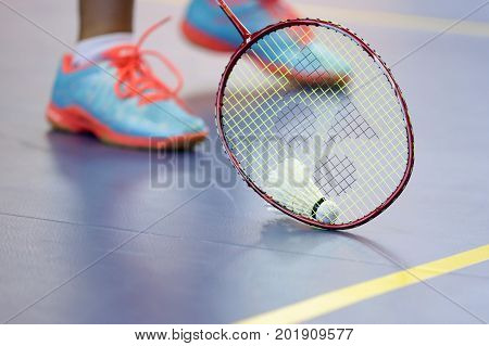 Badminton racket with shuttlecock and player's legs on the court.