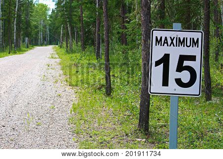 A Maximum 15 Speed Limit Sign Along A Gravel Road.