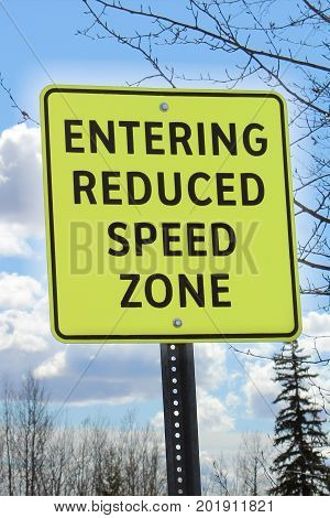 Entering reduced speed zone sign in a residential area
