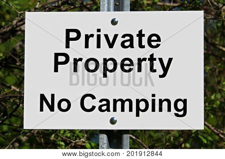 A white private property no camping sign.