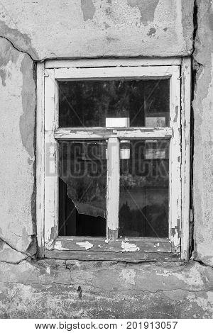 Broken window in the old house. Black and white photography.