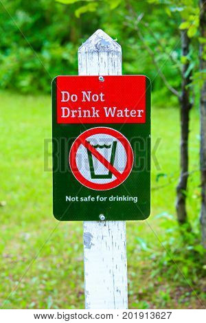 A do not drink water sign with a green background.