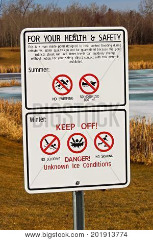Warning and keep off signs around storm drainage pond.