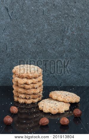 A vertical stack of round nut buttery cookies are laid on a black background with some hazelnuts, sugar drops and a reflection with a copy space