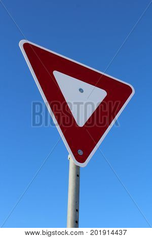 Yield sign isolated against a blue sky.