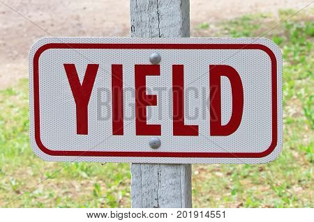 A rectangular yield word sign with grass in the background