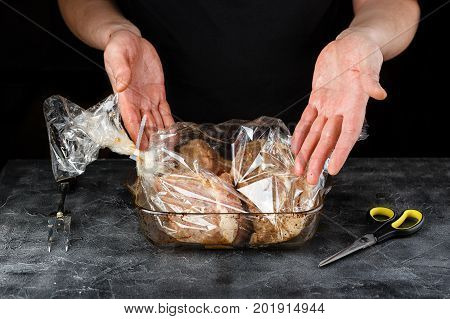 Man stacks marinated meat pieces pork shoulder in the roasting sleeve into glass mold
