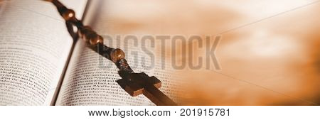 Digital composite of Rosary on bible and blurry orange transition