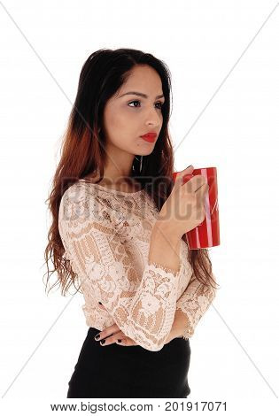 A gorgeous young business woman in a beige blouse and black skirt holding a red big coffee mug looking serious over white background