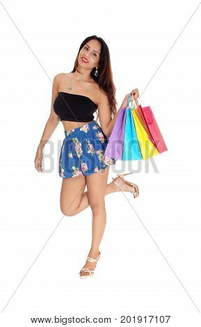 A beautiful young woman standing on one leg smiling holding her colorful shopping bags isolated for white background