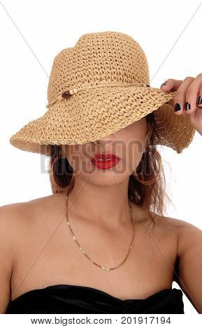 A beautiful mysterious woman with her straw hat over her face in a black dress and red lips isolated for white background