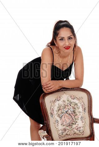 A beautiful young East Indian woman in a black dress standing behind an old armchair smiling isolated for white background