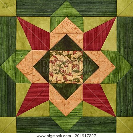 Bright orange-green geometric patchwork block from pieces of fabrics, detail of quilt