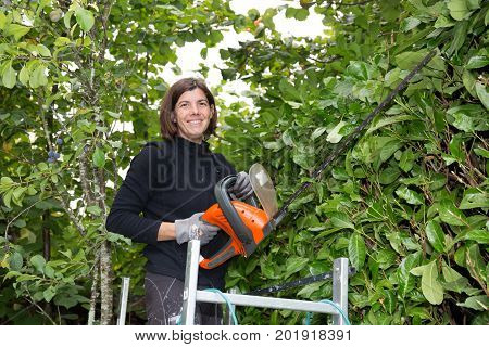 Woman Trimming Her Hedge In The Garden With Electric Hedge Trimmer