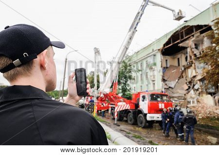 Orel Russia August 29 2017: Collapse of old apartment house. Young man shoots elevating crane on fire truck and EMERCOM rescue team working on ruined building closeup