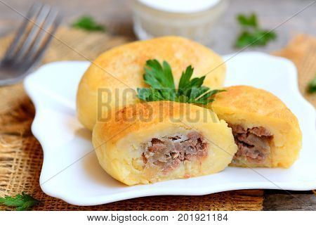 Potato zrazy with a meat filling on a white plate and a vintage wooden table. Traditional Ukrainian zrazy recipe. Closeup