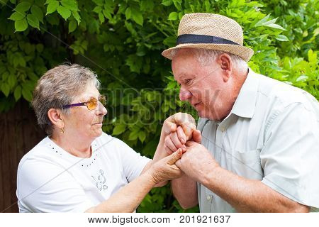 Senior man kissing his wife's hands elderly couple in love outdoor