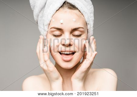Beauty Woman face Portrait. Beautiful model Girl with Perfect Fresh Clean Skin.towel on the head.Youth and Skin Care Concept. Isolated on a white background.Woman applying a cream to face.