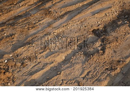 Lifeless   landscape with stones and furrows on the surface of soil