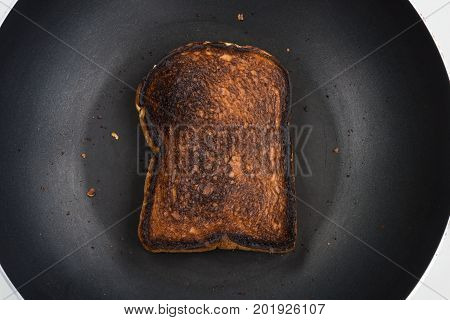 Burnt toasted grains (barley buckwheat corn flaxseed millet rice rye sesame spelt sunflower triticale and wheat) sliced bread with salted butter on black pan over white countertop background