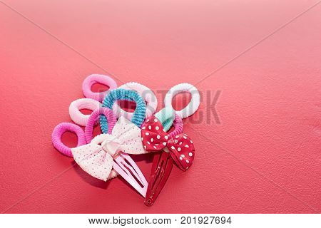 Hair accessories such as elastic bands and buckles in the form of bows. Red background. poster