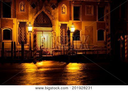 The old doors of a build on the Grand Canal of Venice lite by two lamps.