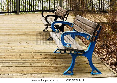 Two colorful benches on a boardwalk path