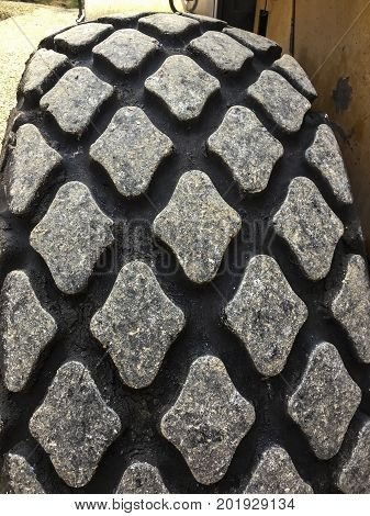 the fragment of the tread of the tyre of the big construction equipment as the background