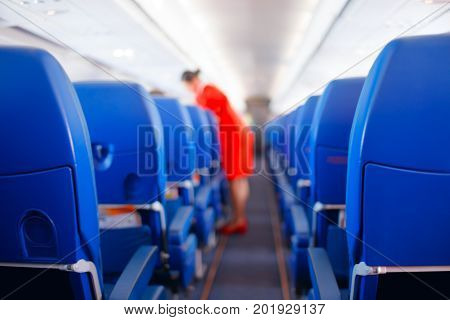 Passenger seat Interior of airplane with passengers sitting on seats and stewardess walking the aisle in background. stewardess serves passengers. Service concept Travel concept.