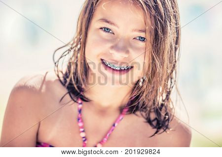Girl with teeth braces. Pretty young teen girl with dental braces. Portrait of a cute little girl on a sunny day in bikini.