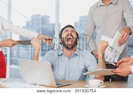 Digital composite of Frustrated business man at a desk yelling