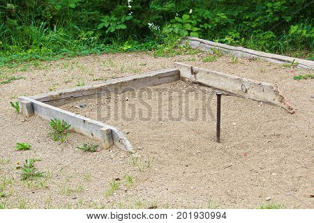 A horseshoe stake in a sandbox area.