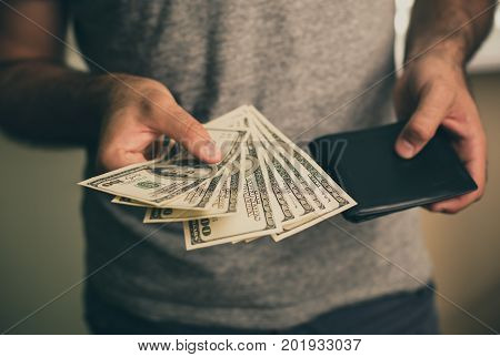 A man in a gray T-shirt holds dollars and black wallet in his hands. Bank. Casino. Salary. Rates.
