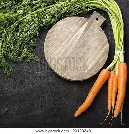 A bunch of fresh juicy carrots with a tops on a dark background with a vintage cutting board and a knife for cooking dinner. Top View