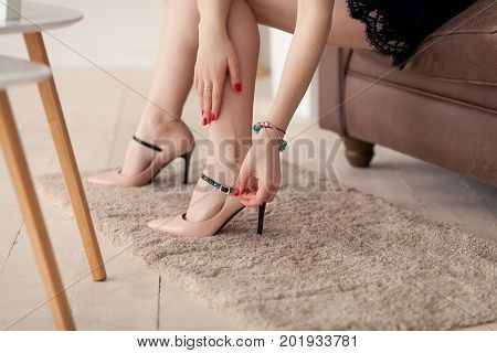 Close up of slim legs of woman wearing high heel beige shoes. Red manicure