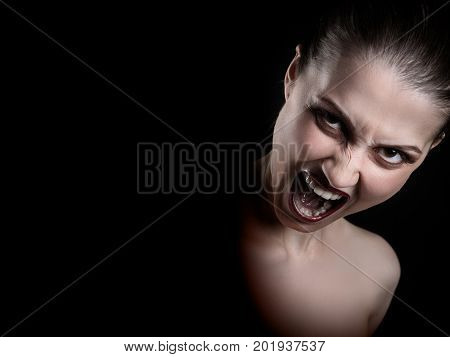angry nude girl screaming at camera on black background with copy space