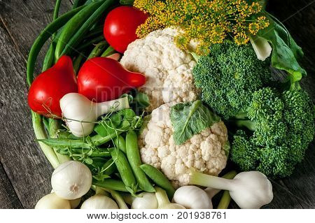Mixed vegetables of cauliflower and broccoli garlic green onions tomatoes and green peas on a wooden background in rustic style for Thanksgiving. A horizontal frame.