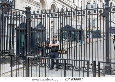 LONDON ENGLAND - JUNE 08 2017: Police officers guards the gate of Downing Street 10 residence of the prime minister in London United Kingdom